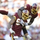 Redskins No. 98 Brian Orakpo jumps on No.  99 Andre Carter